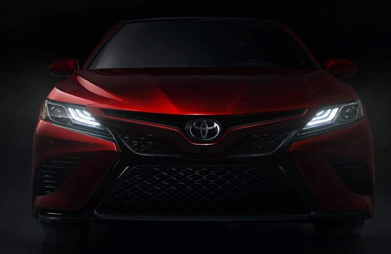 Front profile of red 2018 Toyota Camry with headlights turned on