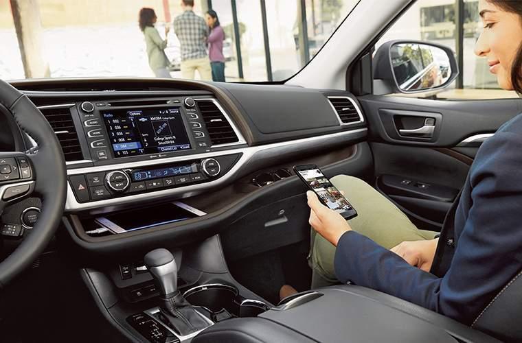 Shotgun rider linking her phone to the Entune infotainment system in the 2018 Toyota Highlander