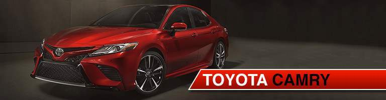 Red 2018 Toyota Camry with dark concrete background