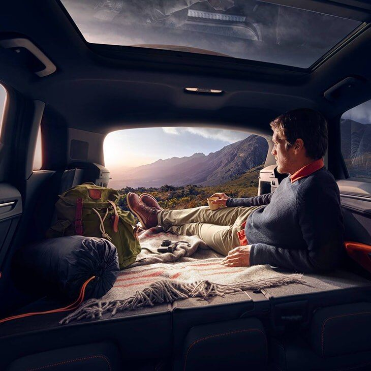 A man lying in the back of the 2019 Q3