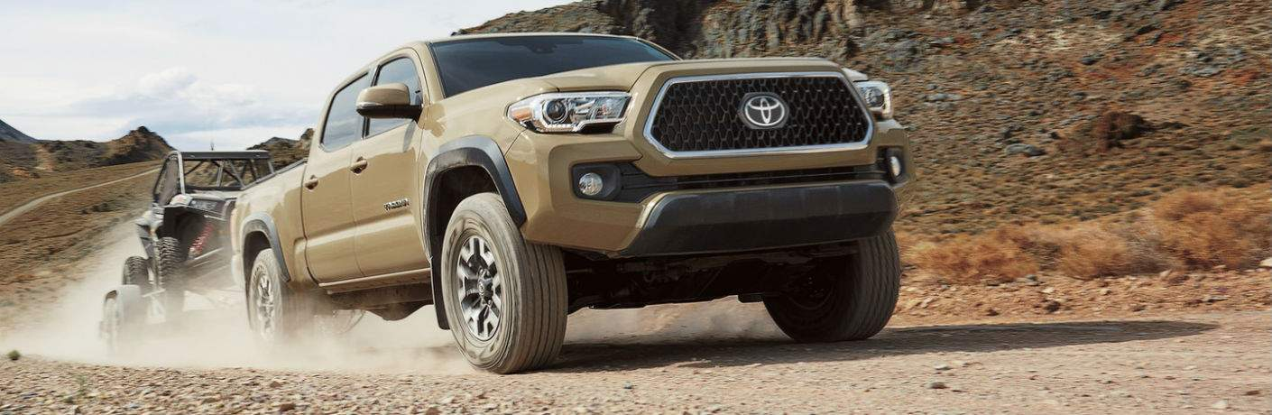 A light brown 2019 Toyota Tacoma towing an off-road vehicle over a rocky trail