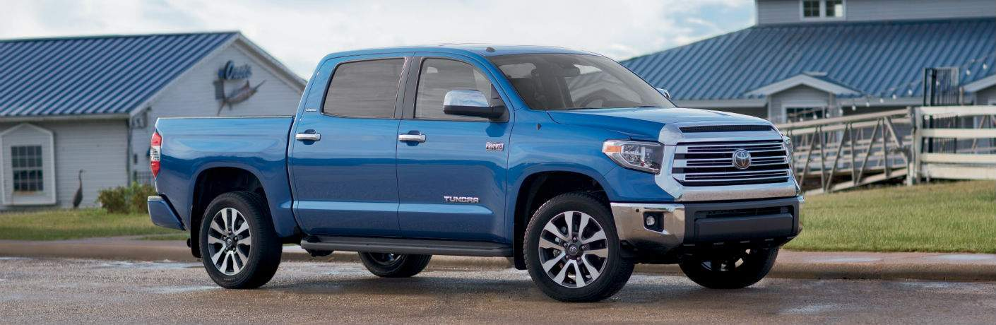 A right profile view of a blue 2018 Toyota Tundra in front of a farm