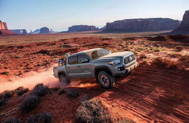 A photo of a 2018 Toyota Tacoma going over a hill on a desert trail
