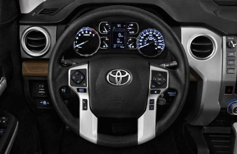 A close up photo of the steering wheel and center gauge cluster for the 2018 Toyota Tundra