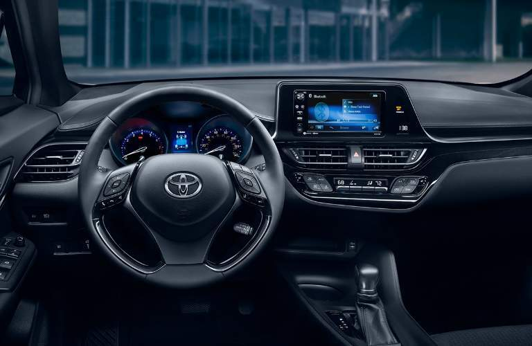 A photo showing the driver's cockpit of the 2018 C-HR including the gauge cluster and infotainment system