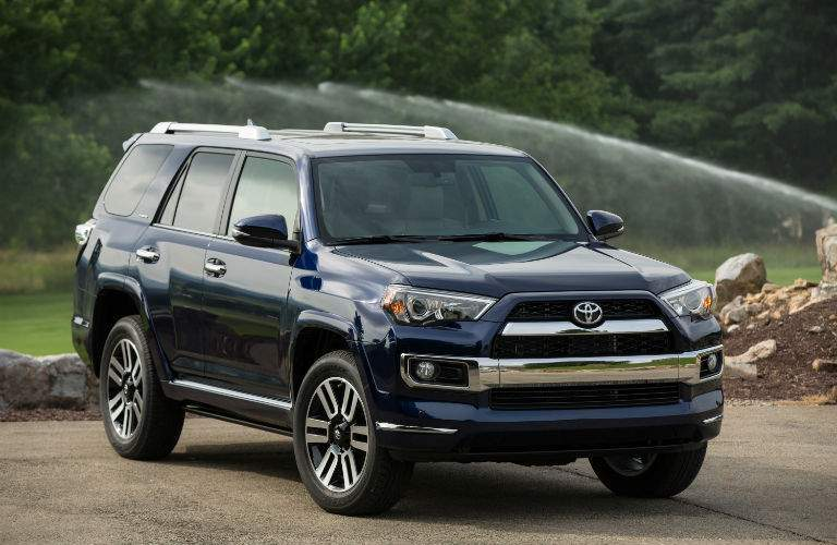 A front left quarter view of a blue 2018 Toyota 4Runner in a driverway
