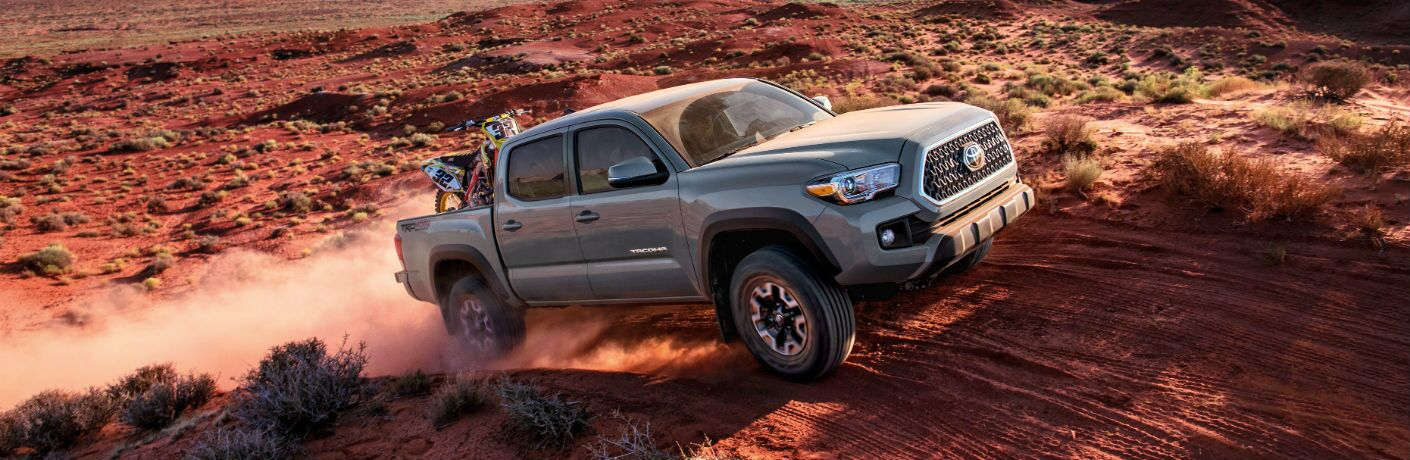 A right profile photo of the 2018 Toyota Tacoma crossing a hill in the desert.