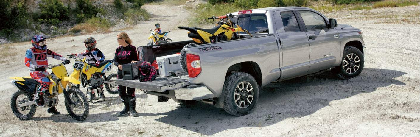 A gray 2018 Toyota Tundra with the TRD off-road package with people loading dirt bikes