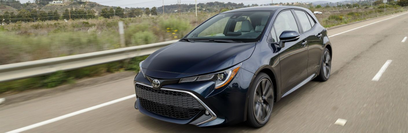 A front left quarter photo of the 2019 Toyota Corolla Hatchback in motion on the road.
