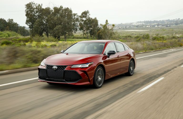 A front left quarter photo of the 2019 Toyota Avalon in motion on the road.