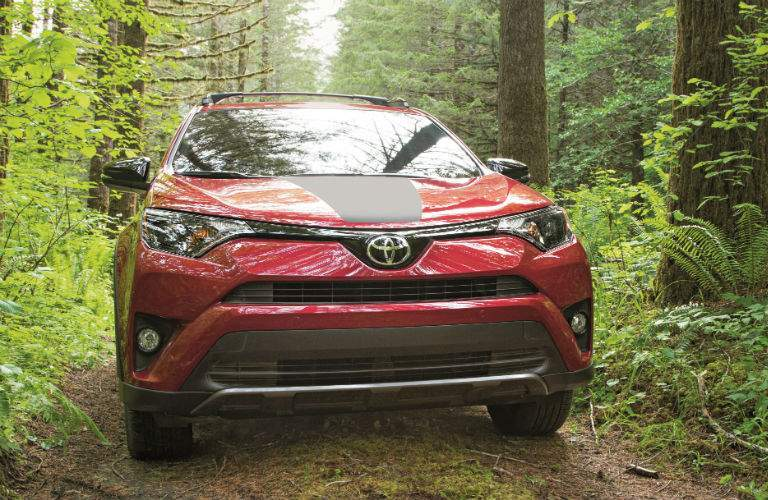 A head-on photo of the 2018 Toyota RAV4 Adventure driving through the woods.