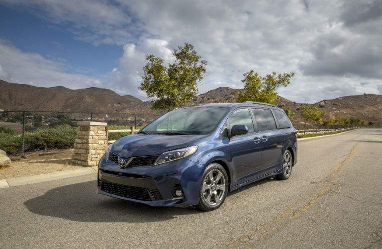 A front quarter view of a blue 2018 Toyota Sienna on a quiet street