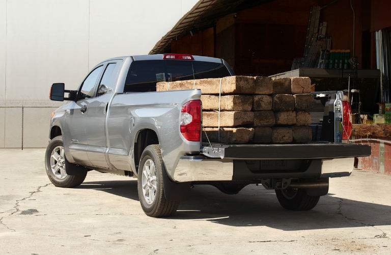 A gray 2018 Toyota Tundra with a heavy load of lumber in the cargo bed, demonstrating its engine power