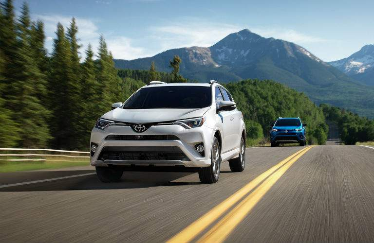 A front view of two versions of the 2018 Toyota RAV4 driving on a road.