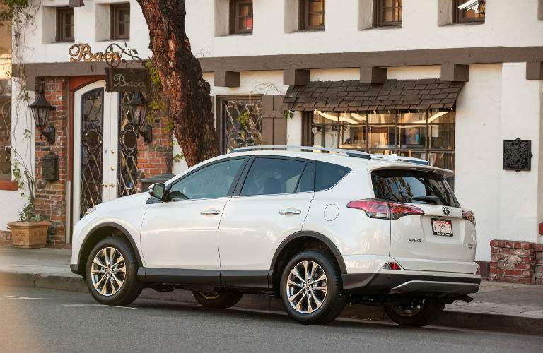 Left profile view of the 2018 RAV4 in front of a small shop in a city