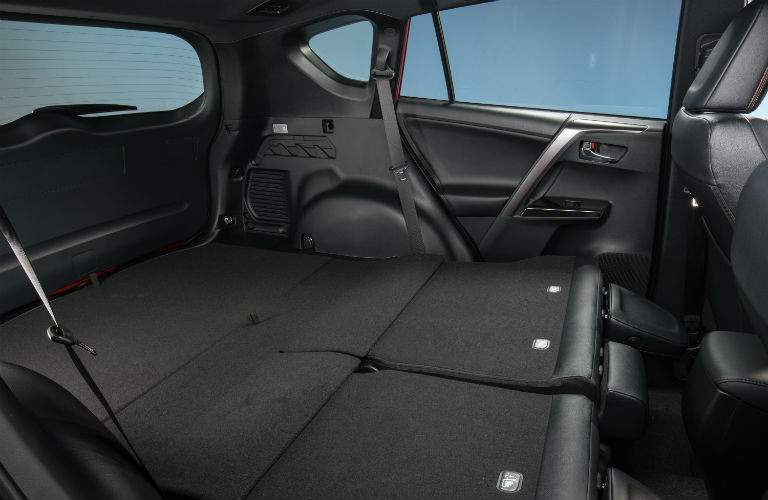 The rear seats are folded down to reveal a large cargo area in the 2018 Toyota RAV4