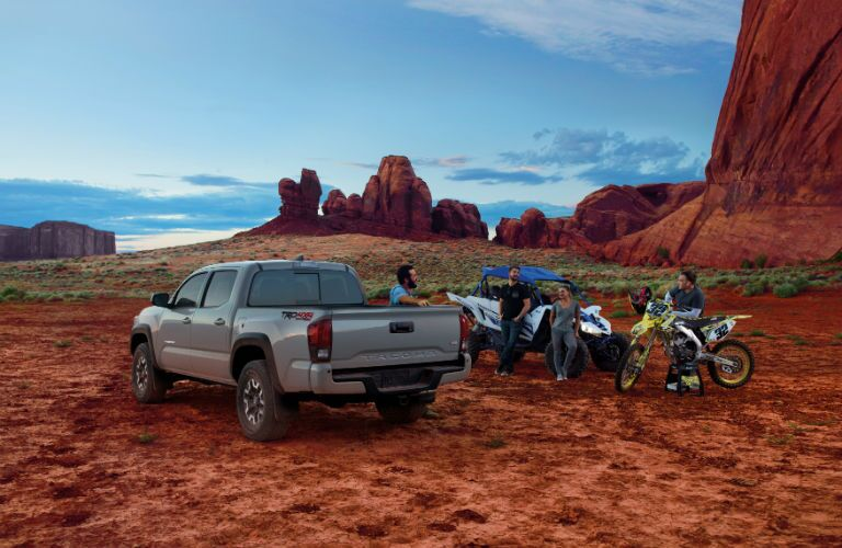 A photo of people standing near the 2018 Toyota Tacoma in the desert.