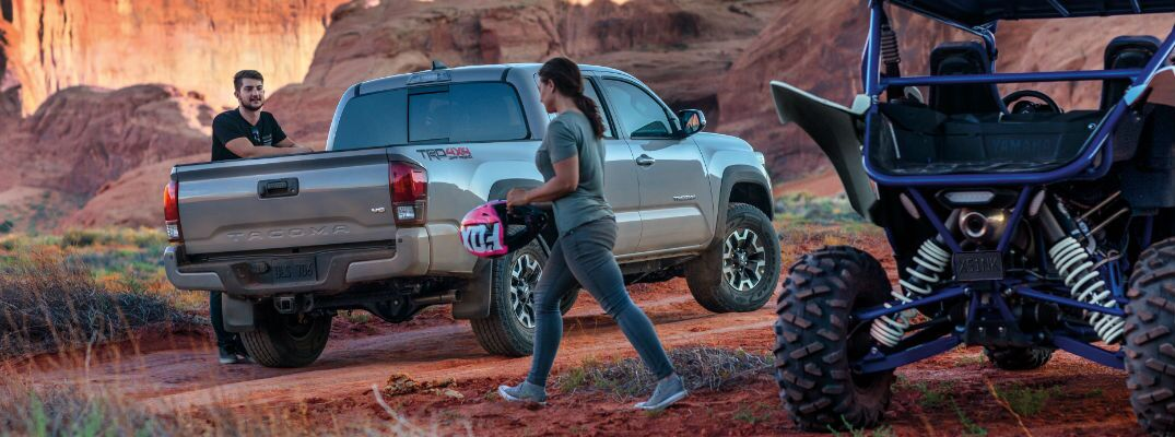 A photo of people getting out of the 2018 Toyota Tacoma in the desert.