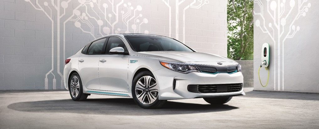 Kia Optima Plug-In Hybrid next to an EV charging station