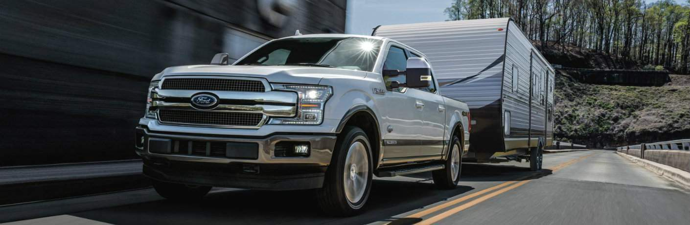 White 2018 Ford F-150 Towing Trailer on Freeway