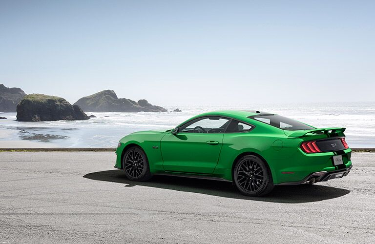 Green 2019 Ford Mustang with Black Racing Stripes Rear Exterior at the Beach