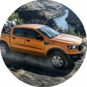 Orange 2019 Ford Ranger with Dirt Bikes in Truck Bed on the Trail