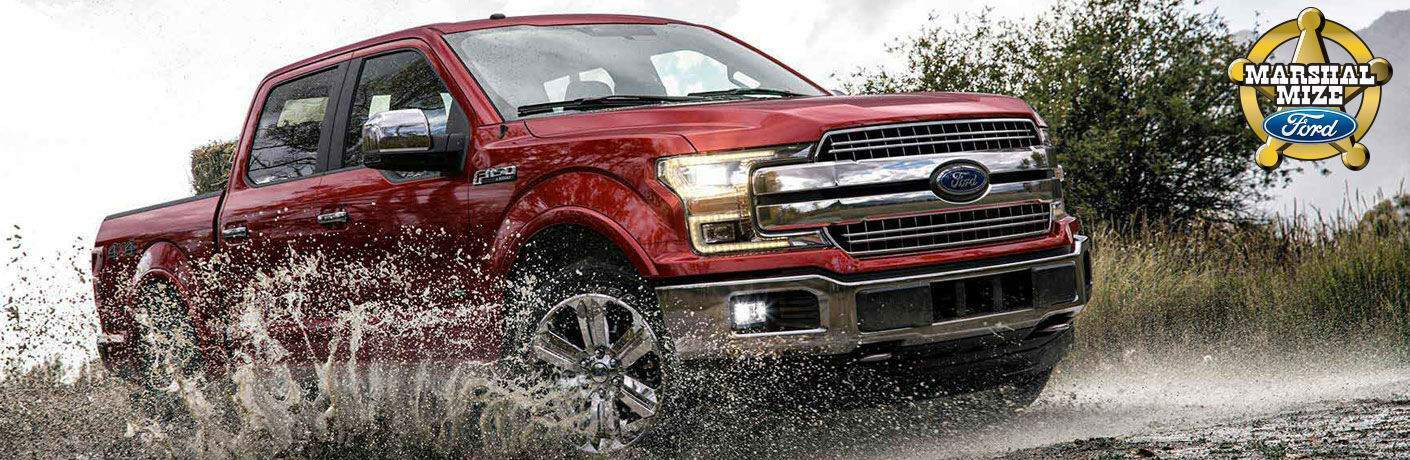 Red 2018 Ford F-150 Driving Through Mud with Marshal Mize Ford Sheriff Badge Logo in Background