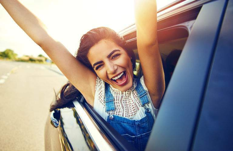 Excited Woman Extending Arms out of Passenger Window of New Car with Smile on Her Face