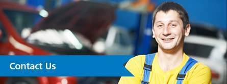 Smiling Mechanic in Yellow Shirt with Blue Contact Us Banner