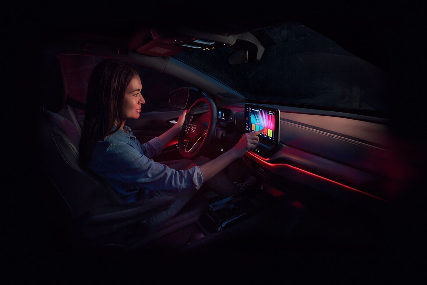 A woman adjusts the ambient lighting inside an ID.4.