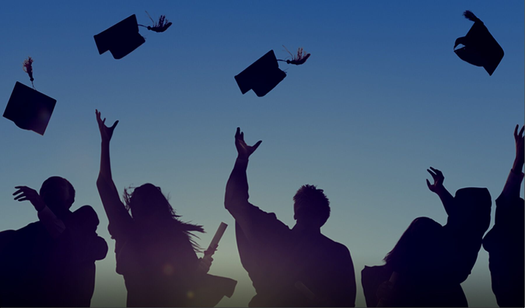 People throwing graduation caps into the air
