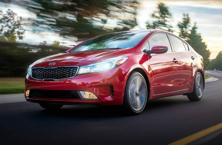 2018 Kia Forte in red driving down the road