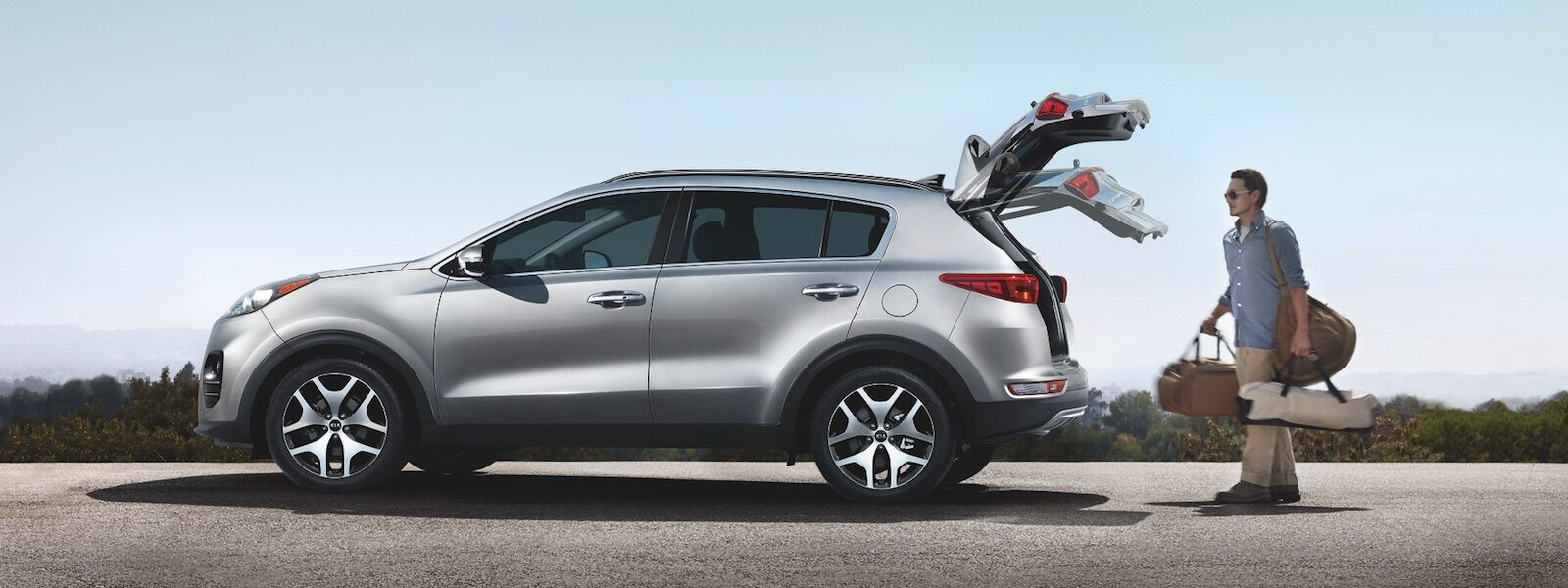 A man opening the trunk on the 2019 Kia Sportage