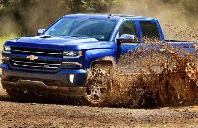 Blue 2016 Chevy Silverado driving through mud