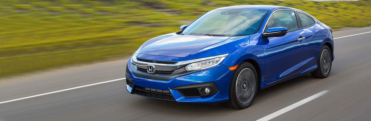 Blue 2018 Honda Civic Coupe driving on highway exterior front driver side view