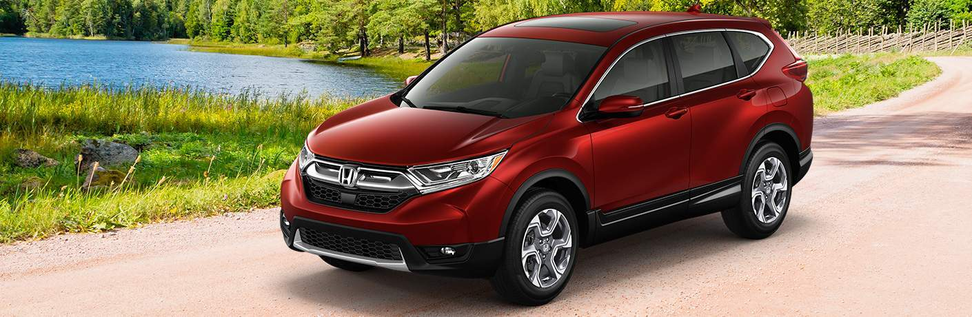 red 2018 Honda CR-V EX-L driving by grassy area and stream