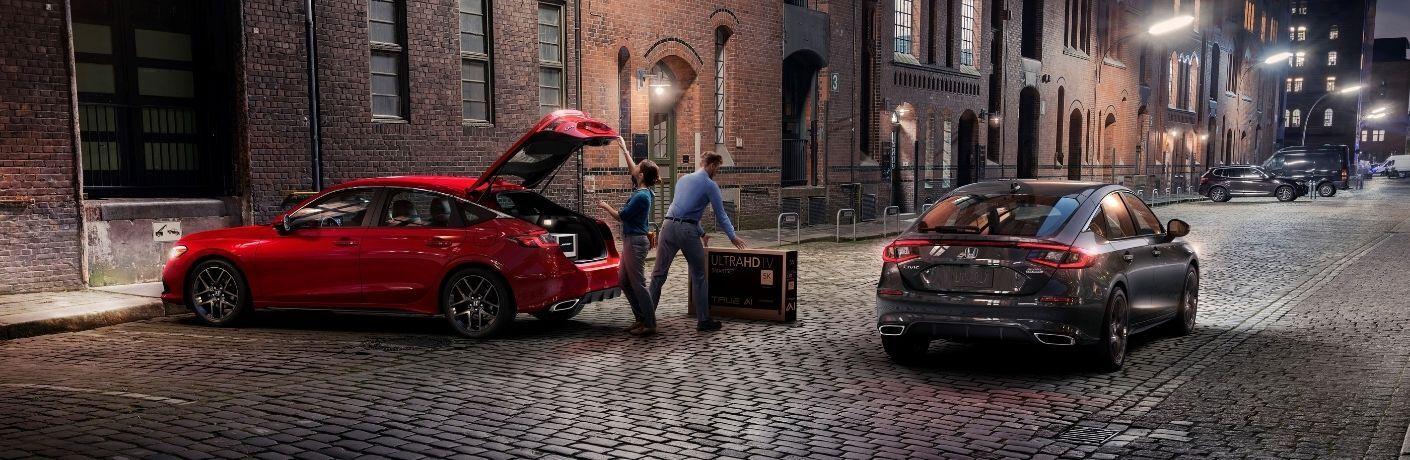 Red and Black 2022 Honda Civic Hatchback Models on a City Street