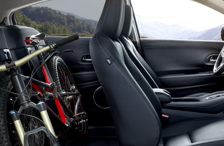 Side view of the interior seats of the 2022 Honda HR-V with a glimpse of the cargo space with a cycle