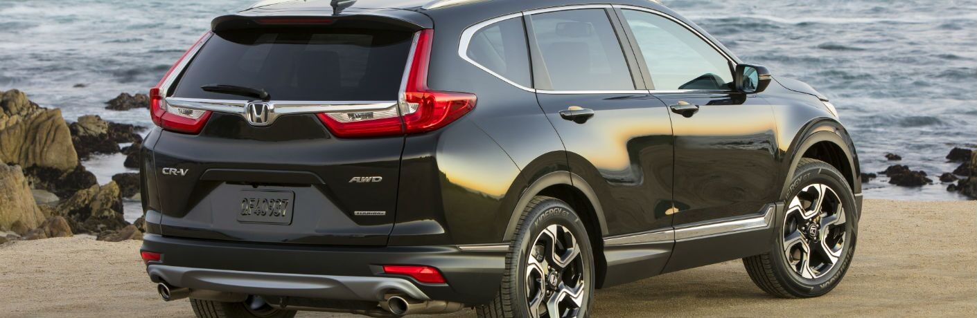 A right rear quarter photo of the 2019 Honda CR-V parked in front of the ocean.