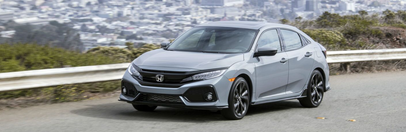 A front-left quarter photo of the 2019 Honda Civic Hatchback on the road.