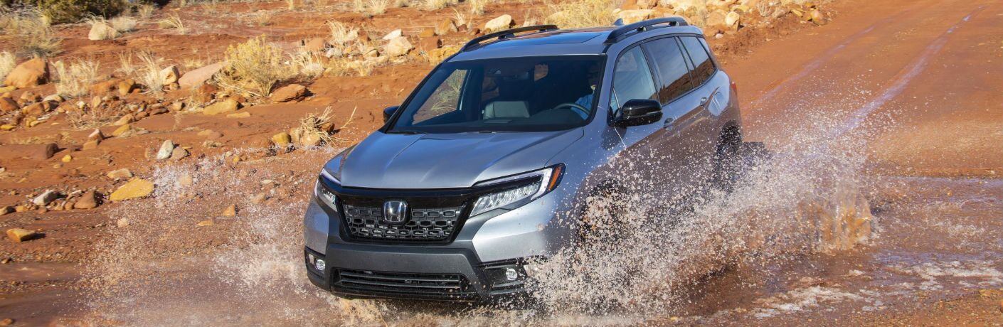 A photo of the 2019 Honda Passport crashing through a mud puddle.
