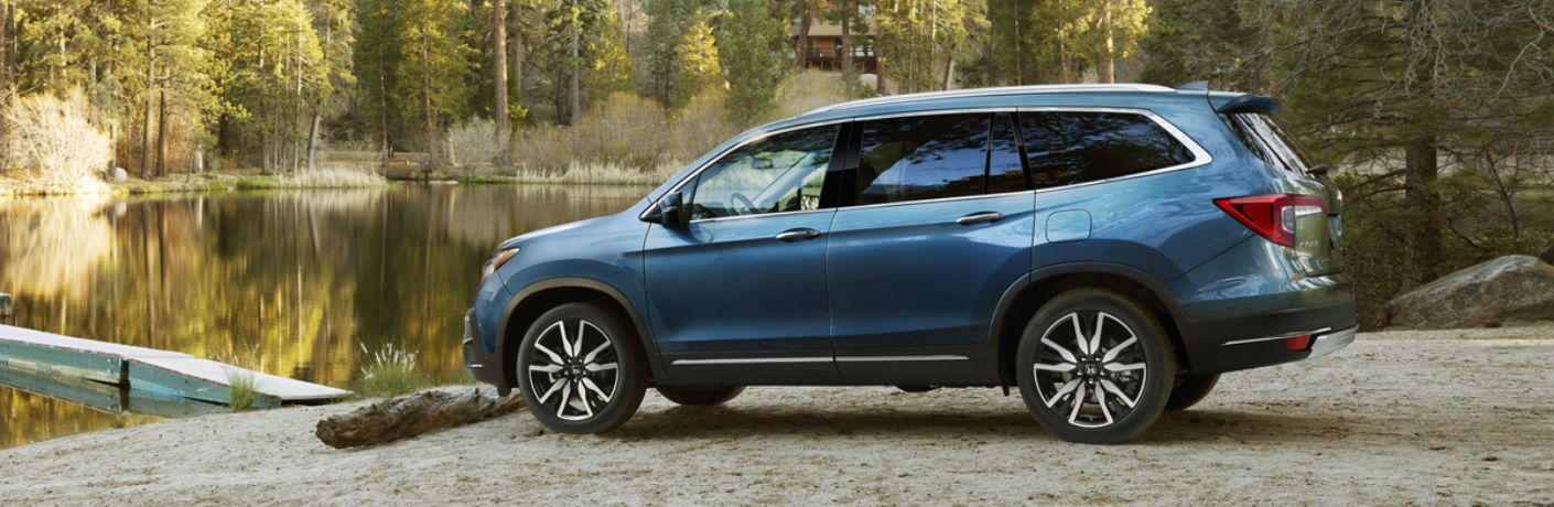 A left profile photo of the 2019 Honda Pilot parked by a lake.