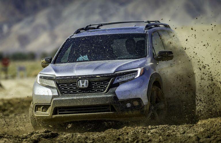 A photo of the 2019 Honda Passport driving through the mud.
