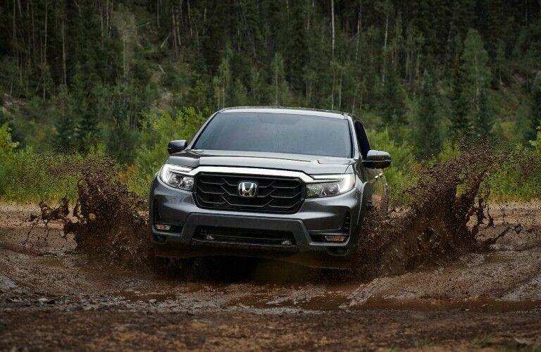 A photo of the 2021 Honda Ridgeline driving through mud.