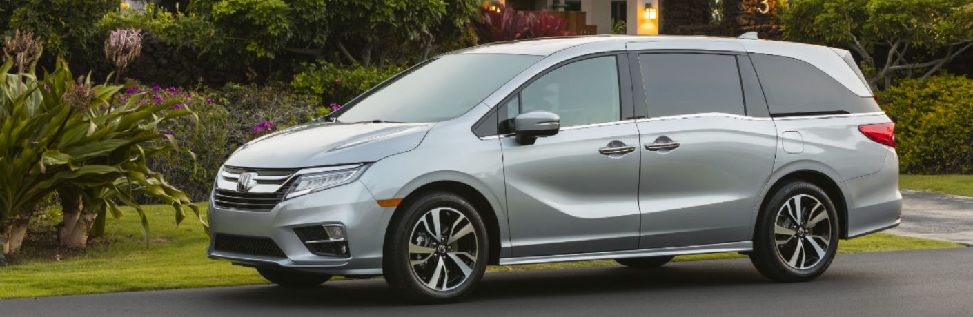 Another left profile photo of the 2020 Honda Odyssey parked in front of a home.
