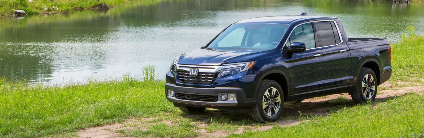 A front-left quarter photo of the 2020 Honda Ridgeline parked by a pond.