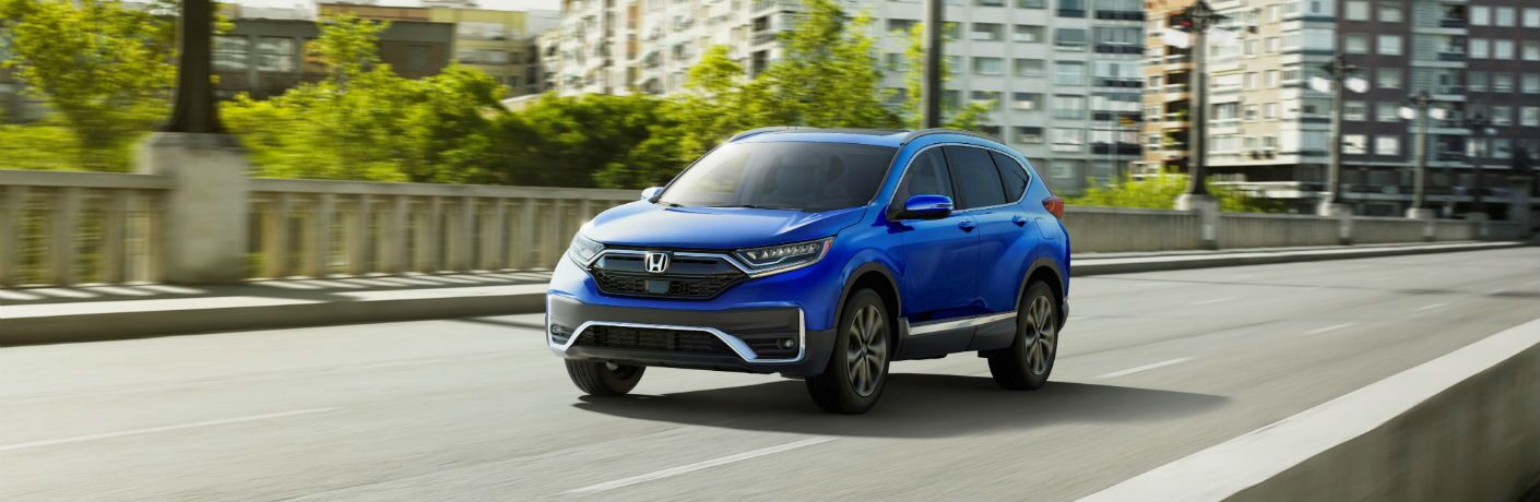 A front left quarter photo of the 2021 Honda CR-V in motion on the road.