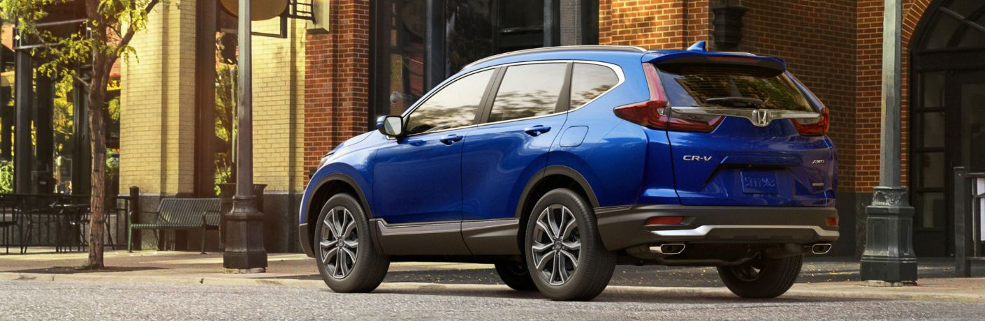 A left profile photo of the 2021 Honda CR-V parked on the street.