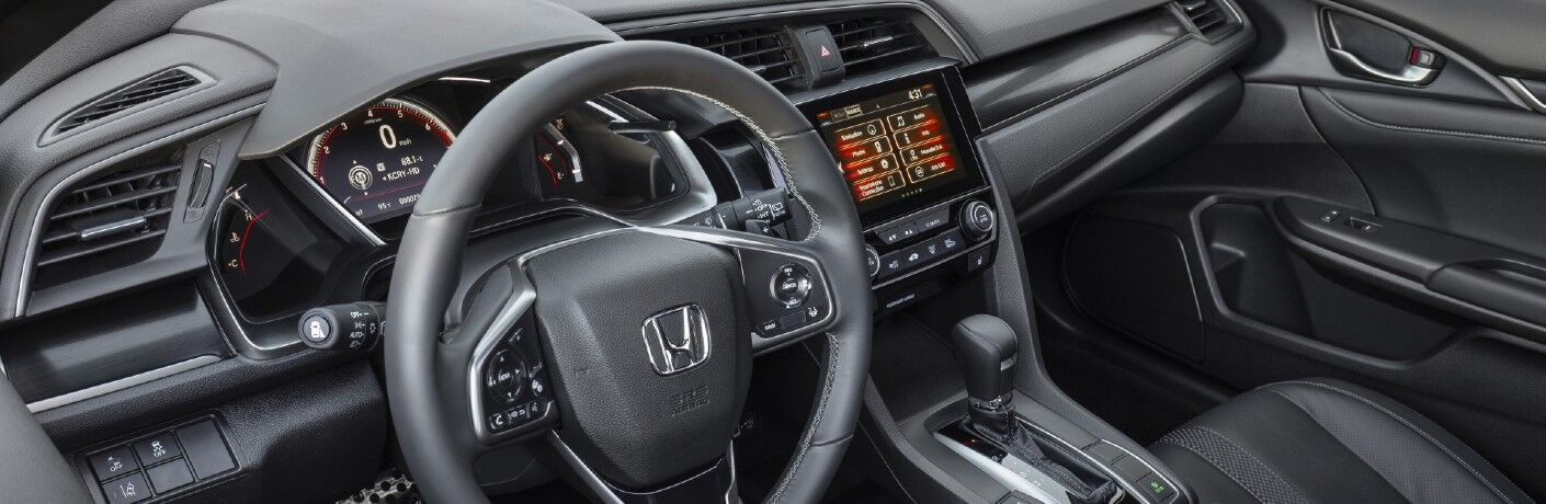 A photo of the driver's cockpit and dashboard in the 2021 Honda Civic Hatchback.