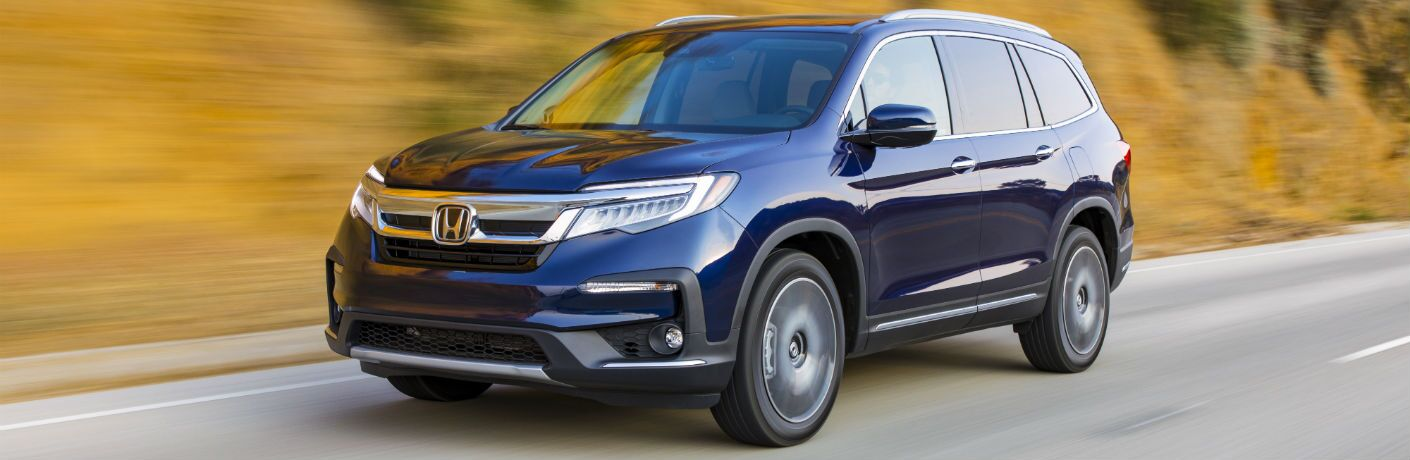 A front left quarter photo of the 2021 Honda Pilot in motion on the road.